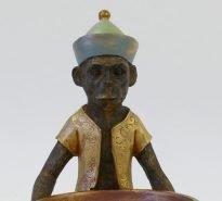 Bronzed monkey holding bowl wearing orange gold jacket